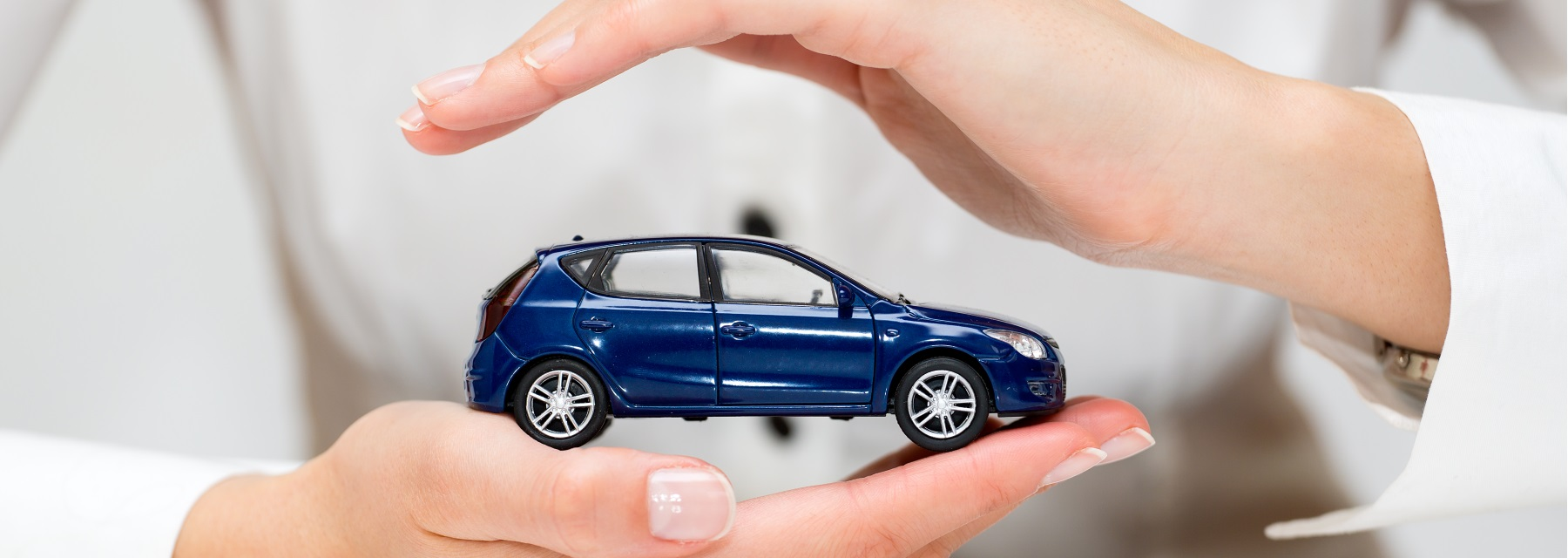 two hands holding miniture blue car